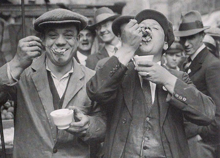 1927 photograph of two men eating jellied eels
